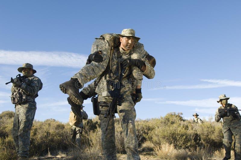 Militaire Mens die een Verwonde Vrouwelijke Solider dragen stock foto's
