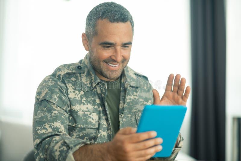 Militaire mens die gelukkig terwijl het zien van zijn familie op het scherm voelen stock foto's