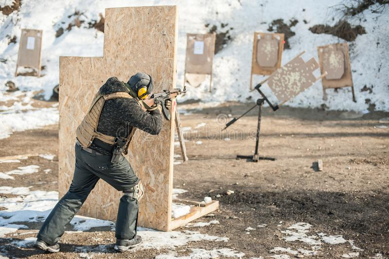 Militaire militair die van geweermachinegeweer schieten op moving target stock afbeeldingen