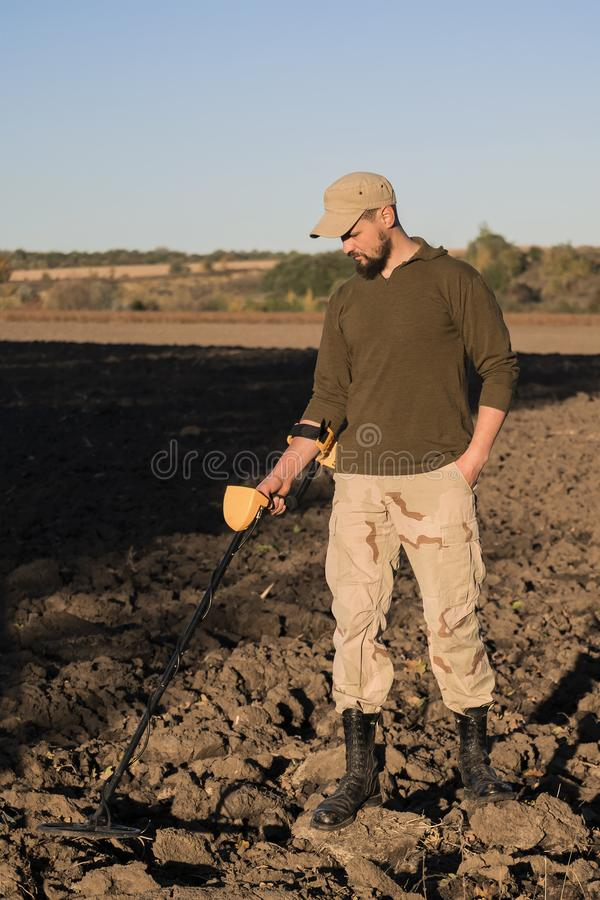 Militaire sapper met een metaaldetector onderzoekt de grond op het gebied voor de aanwezigheid van mijnen royalty-vrije stock afbeeldingen