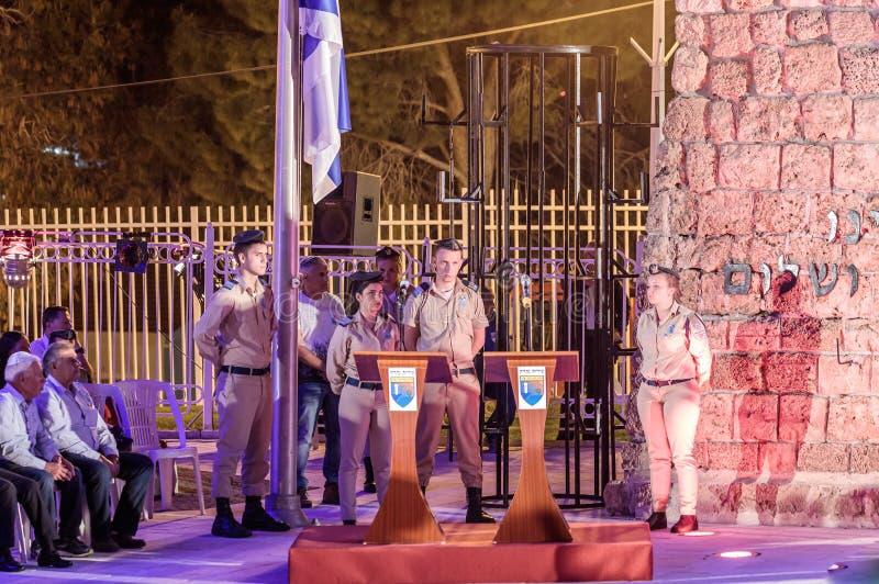 Militairen - de deelnemers van de herdenkingsceremonietribune tijdens een sirene dichtbij helft-masted vlag in de Herdenkingsplaa stock foto