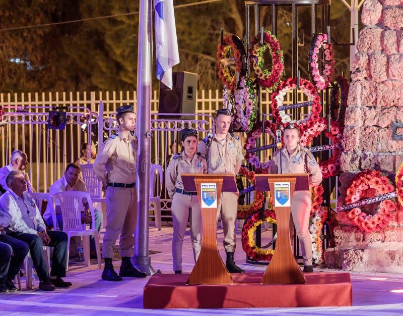 Militairen - de deelnemers van de herdenkingsceremonietribune tijdens een sirene dichtbij helft-masted vlag in de Herdenkingsplaa royalty-vrije stock afbeelding