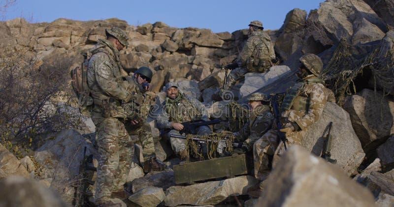 Militairen die een onderbreking van patrouille nemen stock fotografie