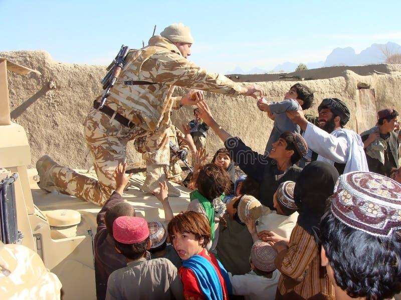 Militairen die hulp in Afghanistan brengen royalty-vrije stock afbeelding