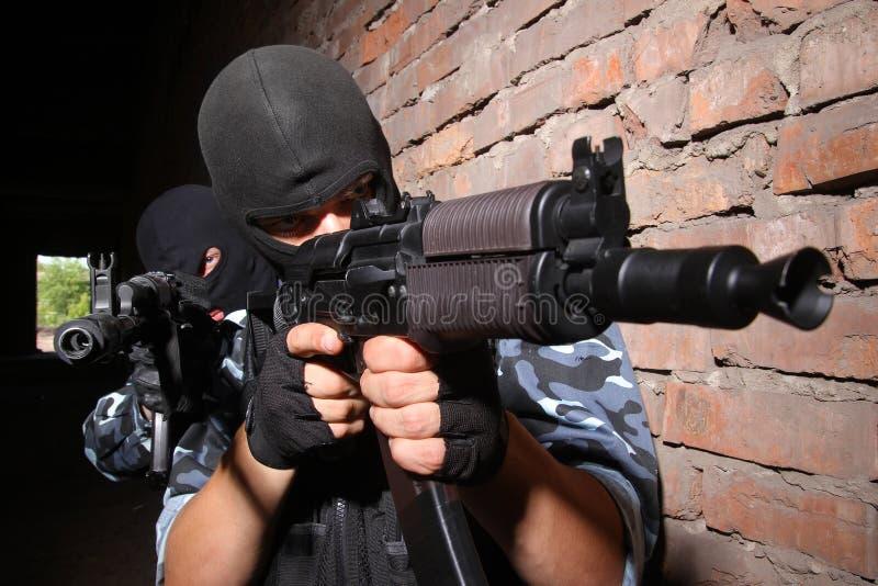 Militairen die in maskers het doel met kanonnen streven stock foto's