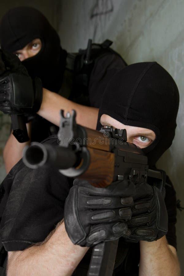 Militairen die in zwarte maskers met geweren richten royalty-vrije stock foto