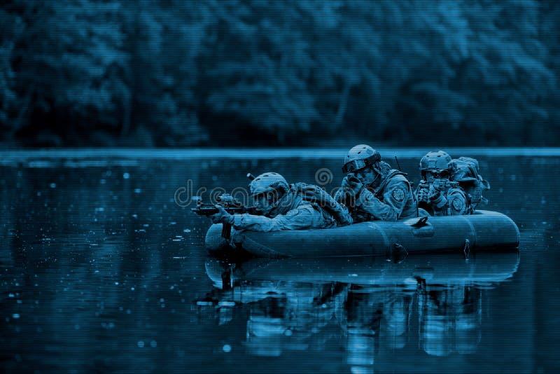 Militairen in een boot die vooruit varen stock afbeelding