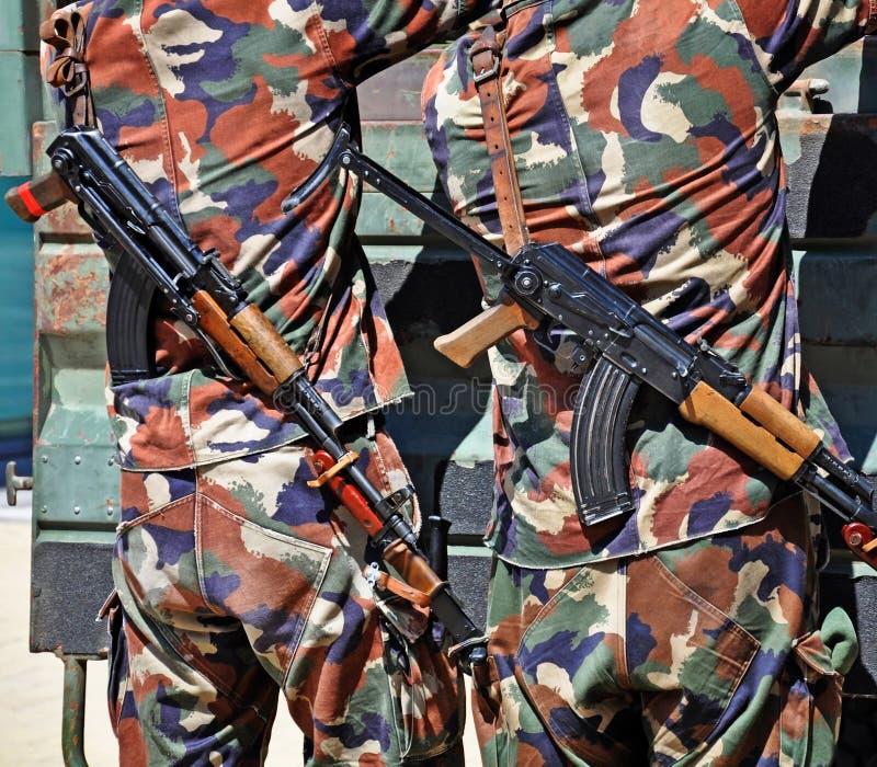 Militairen met machinegeweren in openlucht royalty-vrije stock afbeeldingen