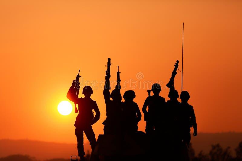 Militairensilhouetten tegen een zonsondergang royalty-vrije stock foto's