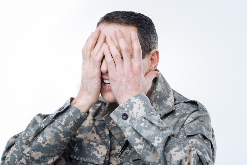 Militar considerável que cobre sua cara foto de stock royalty free