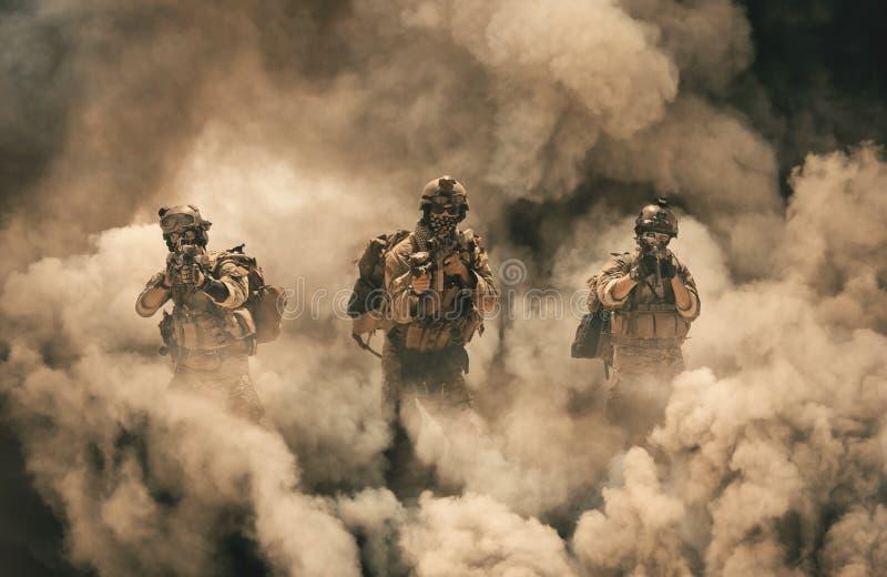 Militar entre o fogo e o fumo na casa destruída fotos de stock