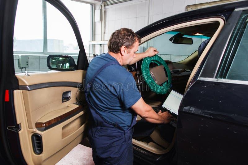 Militar que hace diagnósticos del coche con el ordenador portátil imagen de archivo
