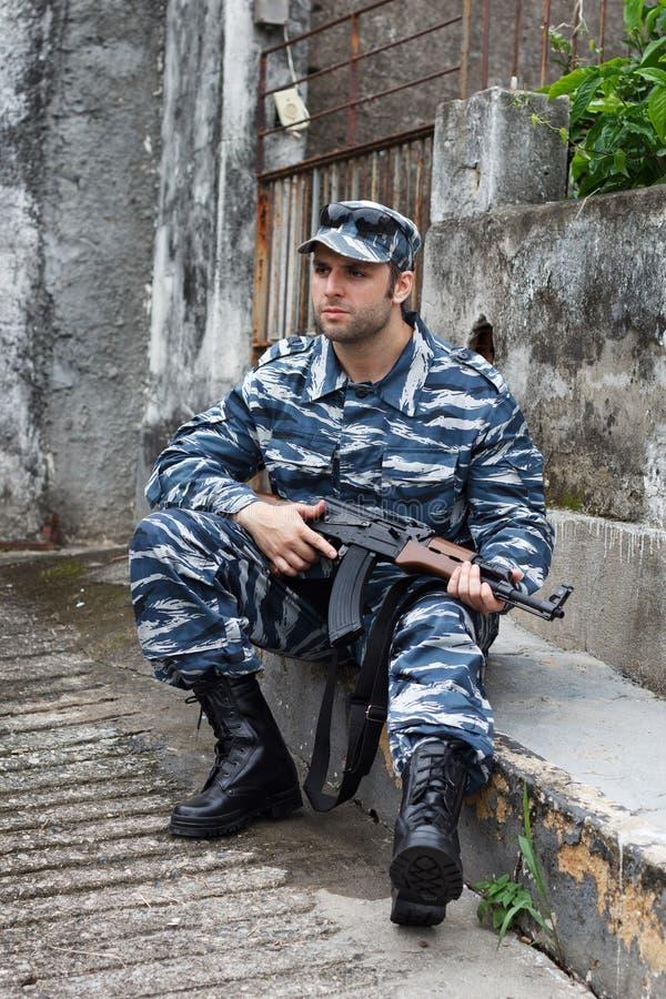 Militare caucasico in auto di seduta e della tenuta di guerra urbana immagini stock