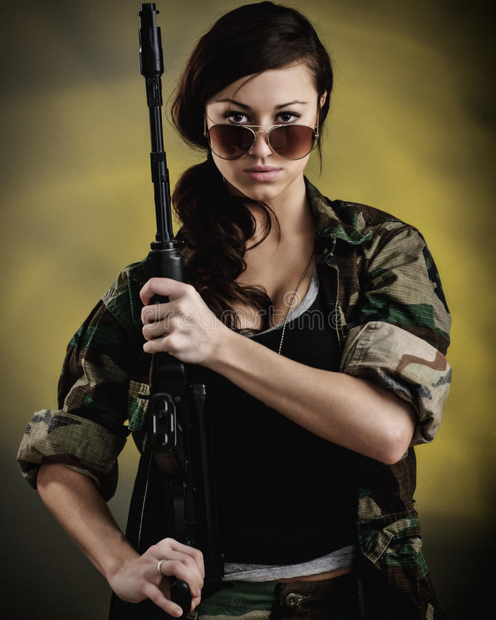 Militarized Young Woman WIth Assault Rifle. A young caucasian woman with an assault rifle stock image