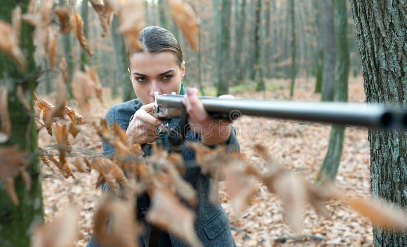 Militarna moda Armatnia bary?ka Osi?gni?cia cele dziewczyna z karabinem go?czy polowanie Armatni sklep żeński myśliwy w lesie obraz royalty free