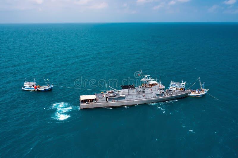 Militarni statki wojenni w morzu trzymać na dystans z łodzią rybacką obraz royalty free