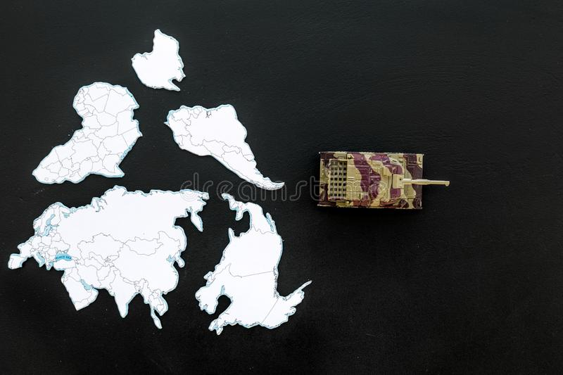 Military action, military threat concept. Tanks toy on world map on black background top view space for text. Military action, military threat concept. Tanks toy stock photography