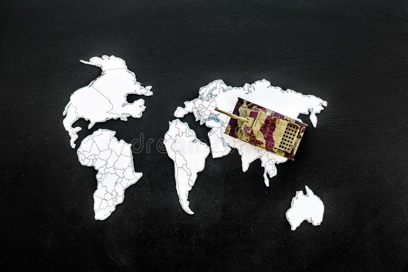 Military action, military threat concept. Tanks toy on world map on black background top view.  stock photos