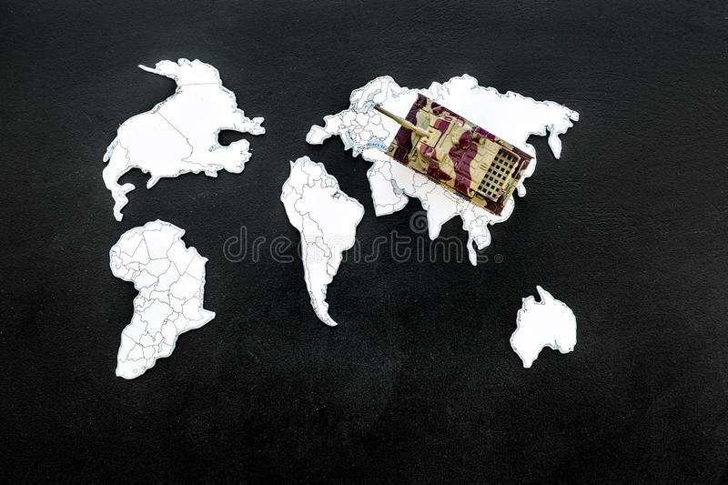 Military action, military threat concept. Tanks toy on world map on black background top view space for text. Military action, military threat concept. Tanks toy royalty free stock photo