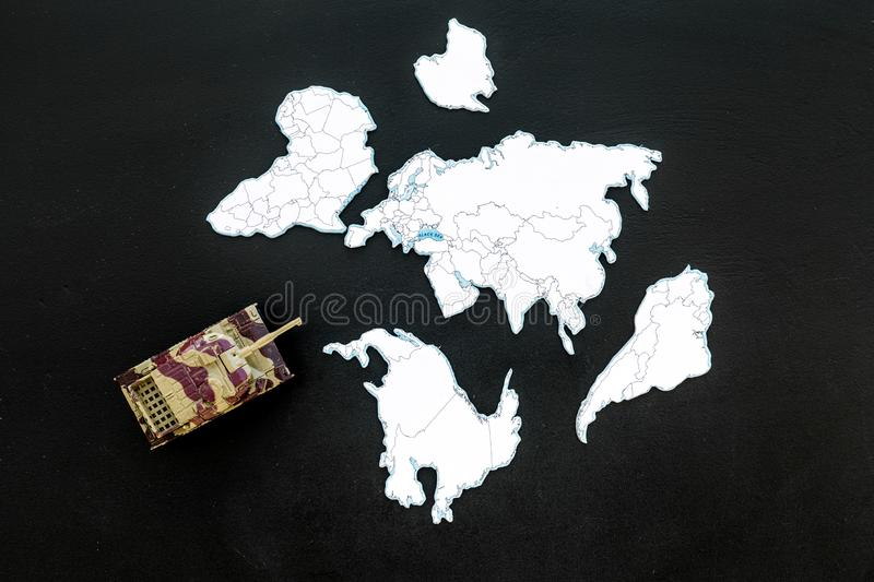 Military action, military threat concept. Tanks toy on world map on black background top view.  stock photography