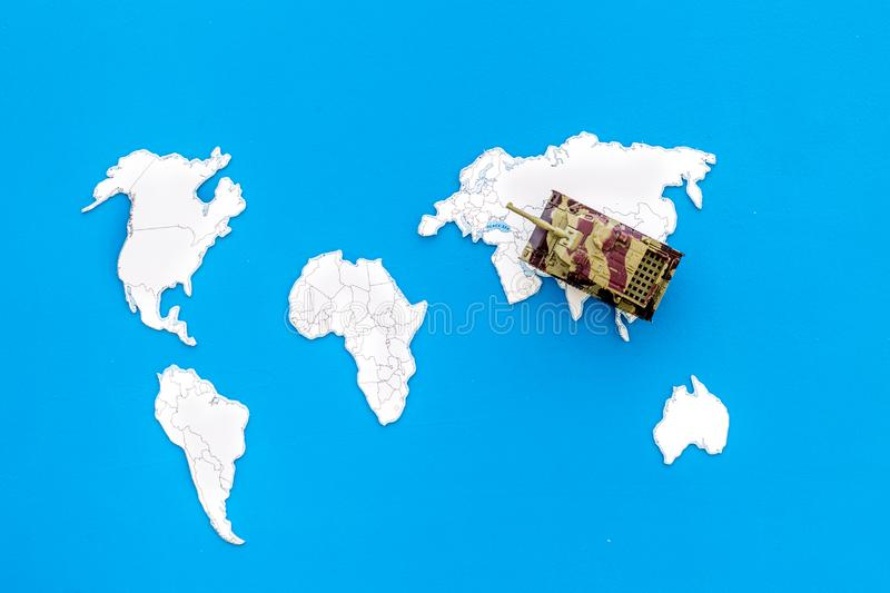 Military action, military threat concept. Tanks toy on world map on blue background top view copy space. Military action, military threat concept. Tanks toy on royalty free stock photos