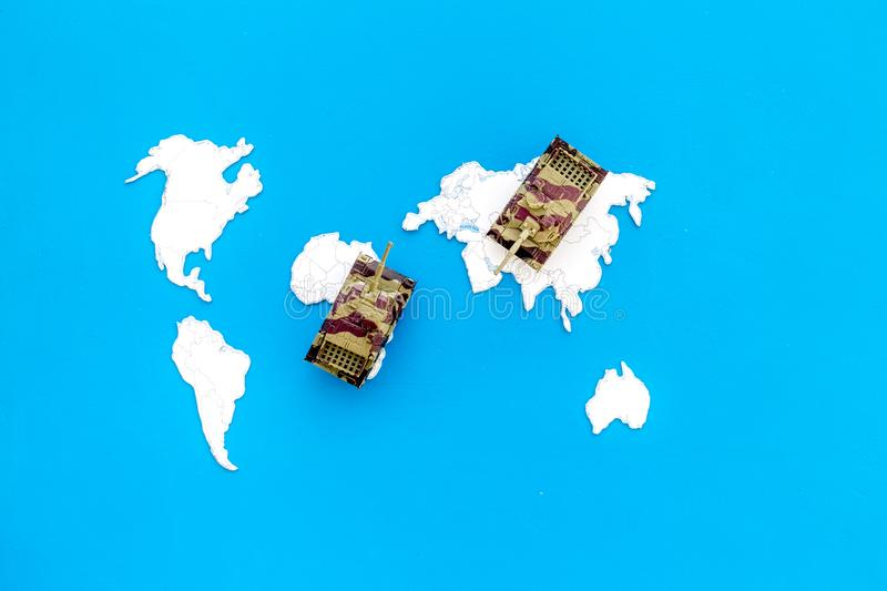 Military action, military threat concept. Tanks toy on world map on blue background top view copy space. Military action, military threat concept. Tanks toy on stock photos