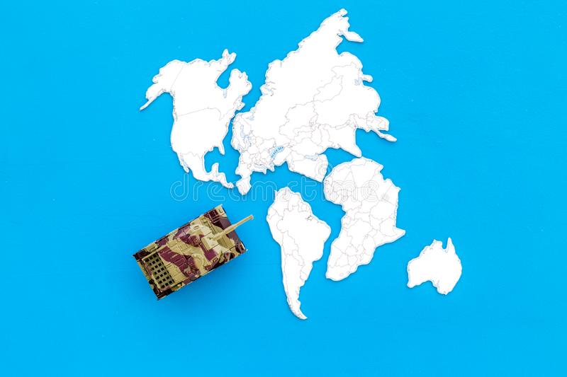 Military action, military threat concept. Tanks toy on world map on blue background top view copy space. Military action, military threat concept. Tanks toy on royalty free stock photo