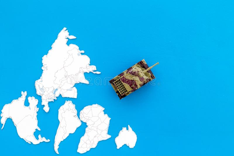 Military action, military threat concept. Tanks toy on world map on blue background top view copy space. Military action, military threat concept. Tanks toy on stock photography