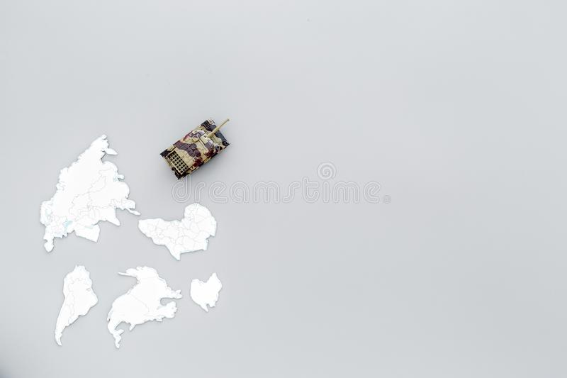Military action, military threat concept. Tanks toy on world map on grey background top view copy space. Military action, military threat concept. Tanks toy on stock image