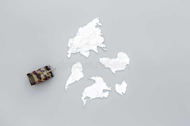Military action, military threat concept. Tanks toy on world map on grey background top view copy space. Military action, military threat concept. Tanks toy on royalty free stock image