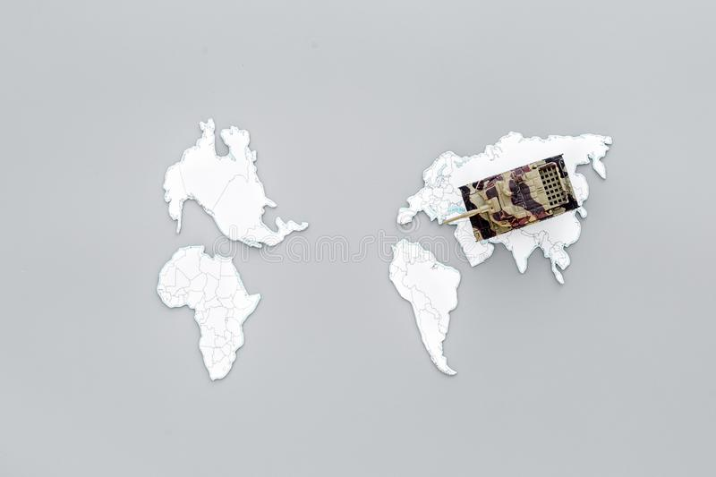 Military action, military threat concept. Tanks toy on world map on grey background top view copy space. Military action, military threat concept. Tanks toy on stock photography