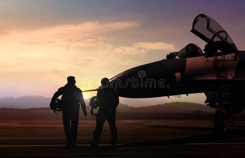 Military Aircraft and pilot at airfield in silhouette scene. During sunset stock image