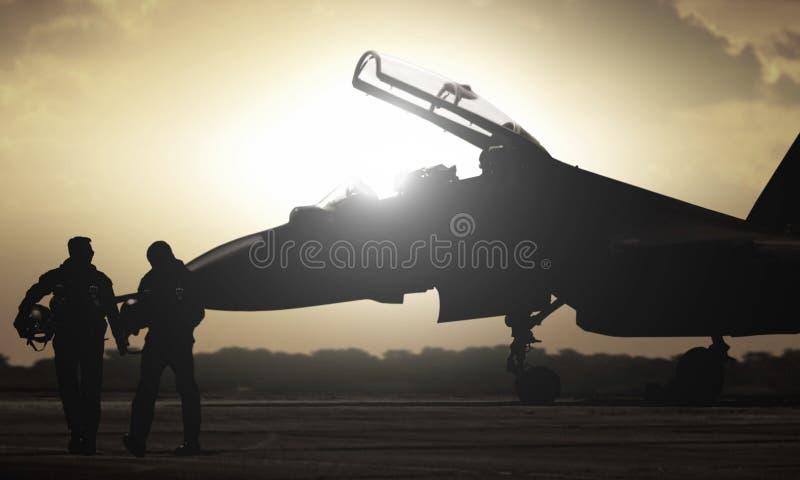 Military aircraft pilot walking during sunset. Military aircraft with two pilot walking during sunset stock photography