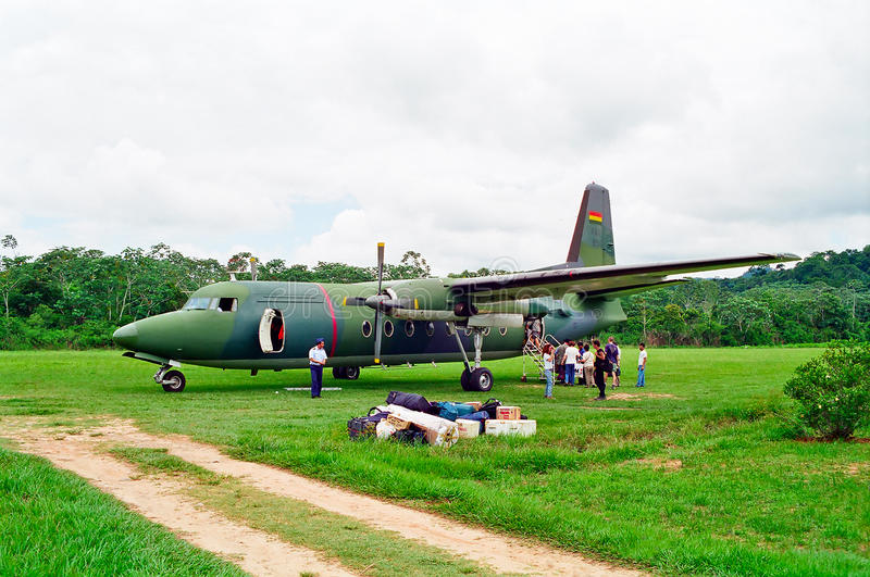 Military Airplane in Jungle, Bolivia. A military airplane being prepared for the next flight on a grass jungle airway, Rurrenabaque, Bolivia royalty free stock image