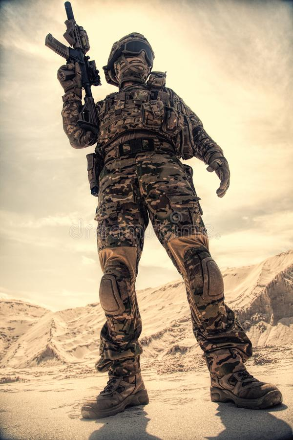 Military airsoft soldier reenactment participant with rifle. Airsoft player in U.S. army uniform, helmet, mask and glasses standing with service rifle replica in royalty free stock photography
