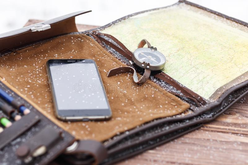 . military bag. compass map and mobile phone. on the wooden background there is natural snow. there is toning. Military bag. compass map and mobile phone. on the stock photo