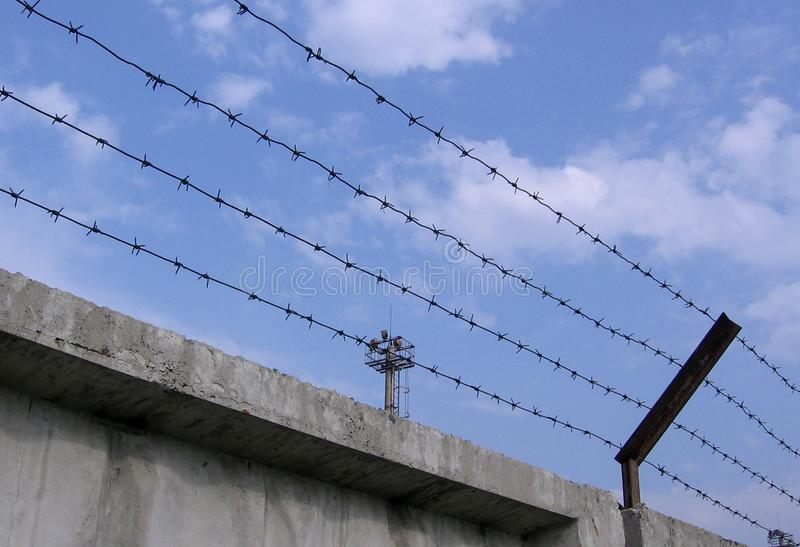 Military base with tower Fence barbed wire fence covers prohibited restricted area industrial strategic facility under protection. The fence is barbed wire on stock images
