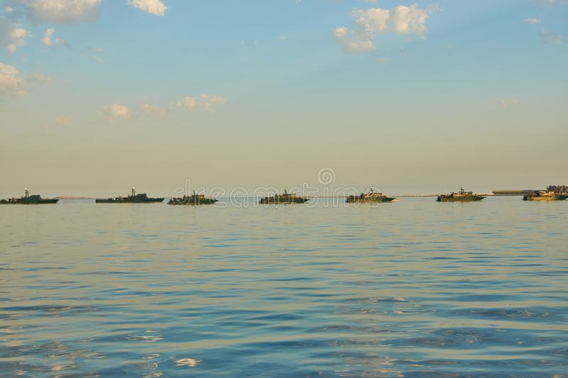 Military Battleships in a sea bay at sunset time. stock image