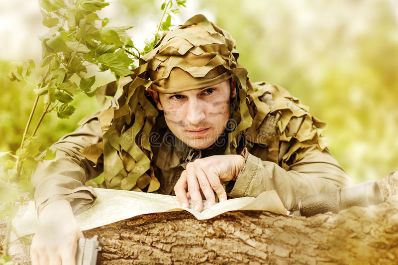 Military Camouflaged man. In forest with black handgun reading map stock photography