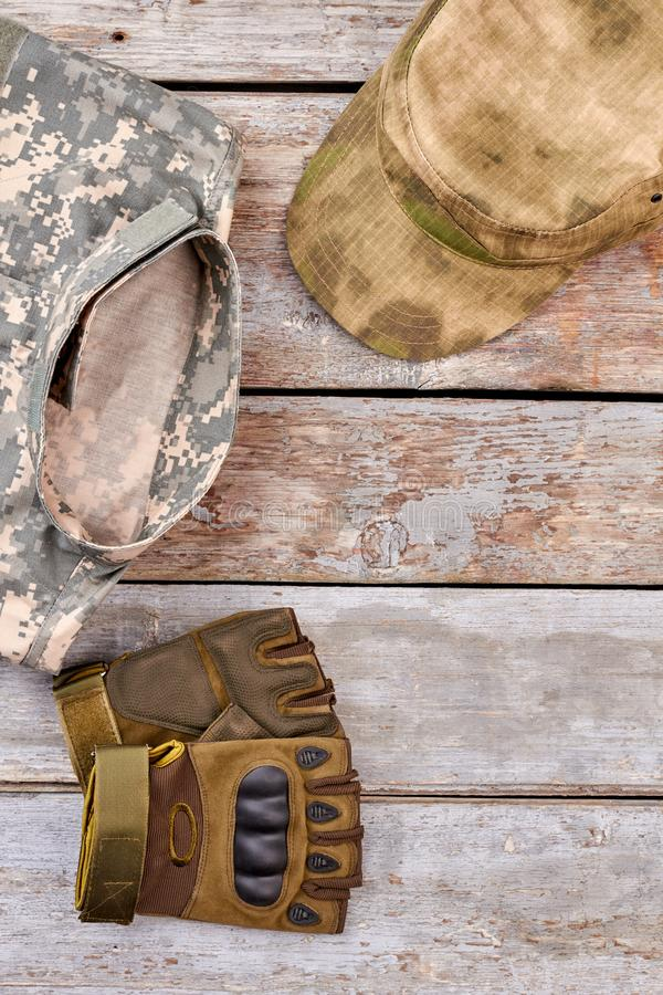 Military clothes, fingerless gloves and cap, close up. Wooden desk background royalty free stock photos