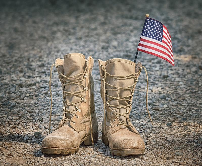 Military combat boots with the American flag. Old military combat boots with the American flag. Rocky gravel background. Memorial Day or Veterans day concept royalty free stock photos
