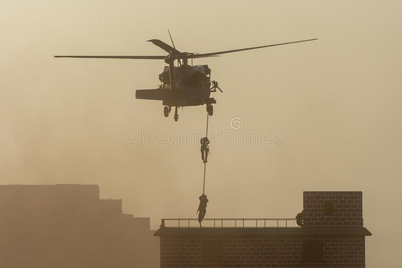 Military combat and war with helicopter flying into the chaos and destruction. Soldiers suspend from rope to the ground from royalty free stock photo