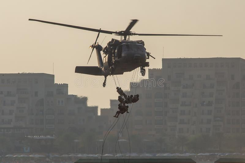 Military combat and war with helicopter flying into the chaos and destruction. Soliders suspend from rope to the ground from stock photography