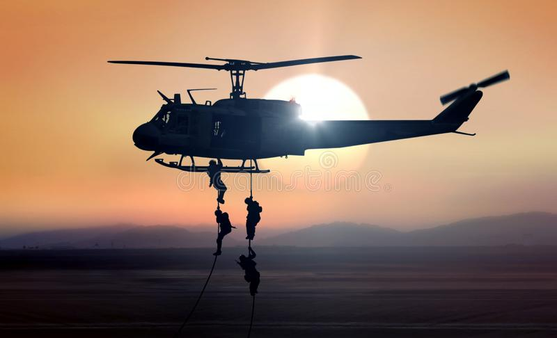 Military commandos helicopter drops during sunrise. Military commandos units helicopter drops during sunrise royalty free stock photo