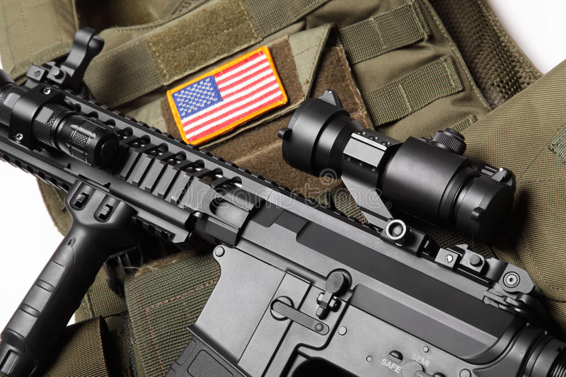 Military concept. Green tactical body armor with U.S. stripe flag and M4A1 assault rifle close-up. Studio shot stock images