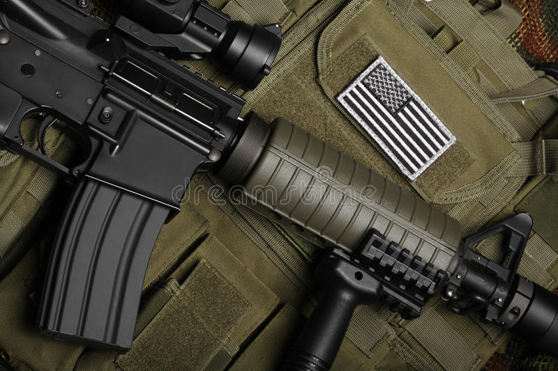 Military concept. Still life. Military concept, still life. Tactical vest with U.S. battle flag and assault rifle with red-dot sight and tactical grip close-up stock photos