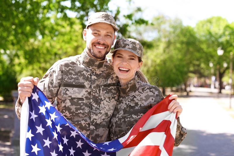 Military couple with American flag. In park stock photography