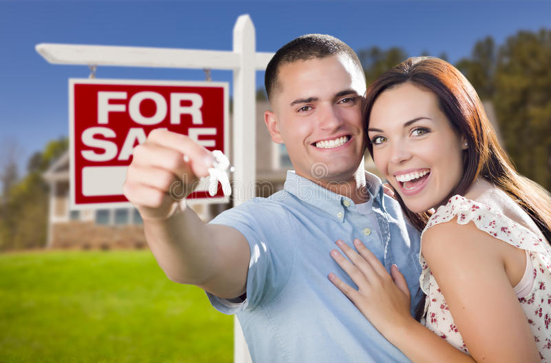 Military Couple In Front of Home, House Keys and Sign. Mixed Race Excited Military Couple In Front of New Home with New House Keys and For Sale Real Estate Sign stock photography