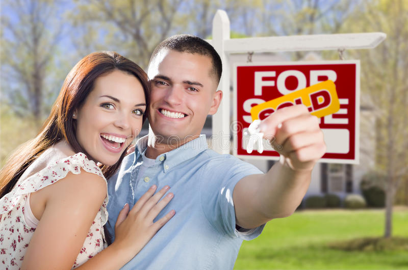 Military Couple In Front of Home, House Keys and Sign. Mixed Race Excited Military Couple In Front of New Home with New House Keys and Sold Real Estate Sign stock image