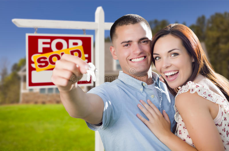 Military Couple In Front of Home, House Keys and Sign. Mixed Race Excited Military Couple In Front of New Home with New House Keys and Sold Real Estate Sign stock photos